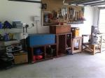"Left to Right:  Shelf with misc. storage & jointer, power tool storage locker & movable shelves, power planer stand, pegboard with hand tools, bandsaw/router table (it's now on 3"" castors)"